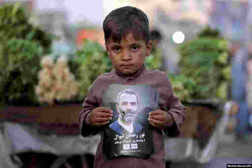 An Afghan child who works in a bazaar on the outskirts of Kabul holds a poster of presidential candidate Noor Rahman Liwal. (AP/Ebrahim Noroozi)