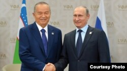 Islam Karimov and Vladimir Putin shake hands in 2015.