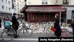 Люди стоят у ресторана Le Carillon, на который было совершено нападение. Париж, 16 ноября 2015 года.