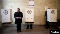 A man holds his ballot at a polling station in Yerevan during parliamentary elections on May 6.