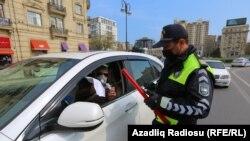 Азербайджанский полицейский в маске проверяет документы водителя остановленного автомобиля в Баку.
