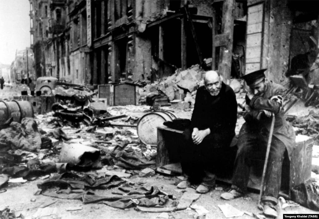 """Слепой человек (справа) и его проводник на берлинской улице, 1945 год. Халдей вспоминал, что спросил слепого на немецком - """"Откуда вы?"""". Тот ответил: """"Мы больше не знаем. Мы не знаем, откуда мы и куда мы направляемся""""."""