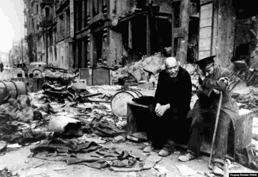 """A blind man (right) with his escort on the ruined streets of Berlin in 1945. Khaldei remembers asking the men in German where they had come from. The blind man responded, """"We don't know anymore. We don't know where we've come from, or where we're going."""""""