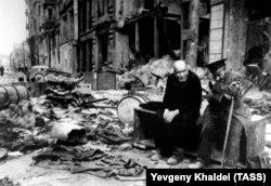 Слепой человек (справа) и его проводник на берлинской улице, 1945 год. Халдей вспоминал, что спросил слепого на немецком: «Откуда вы?». Тот ответил: «Мы больше не знаем. Мы не знаем, откуда мы и куда мы направляемся».