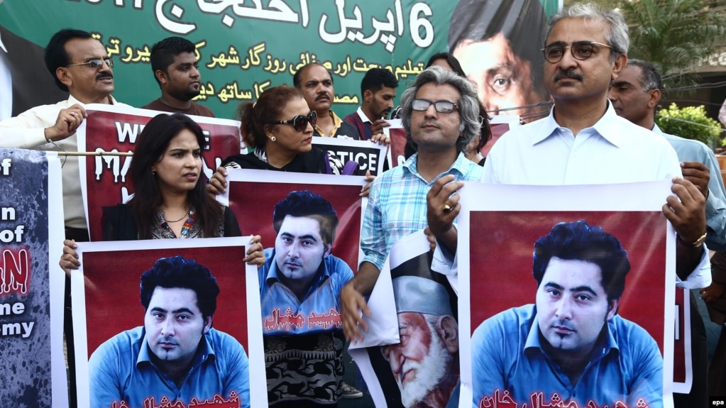 During a rally in Karachi, people hold portraits of Pakistani student Mashal Khan, who was killed by a mob for alleged blasphemy at Abdul Wali Khan University in April.