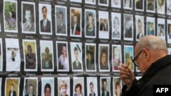 A man crosses himself in front of the portraits of the hostage-drama victims at the Dubrovka Theatre in Moscow.