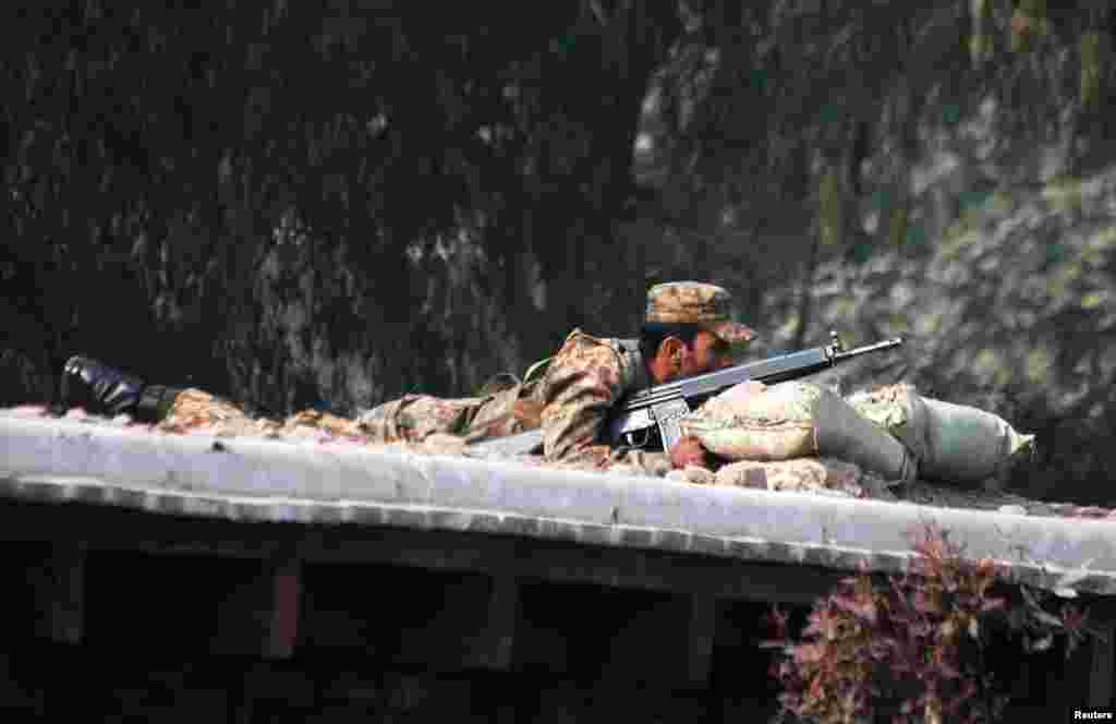 A Pakistani soldier takes up a position above a road near the military school.