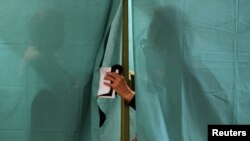 People are seen behind the curtain of a voting booth in Minsk during parliamentary elections on September 23.