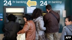 People withdraw money from an ATM in the Cypriot capital Nicosia. A proposed tax on savings has caused outrage in the island country.