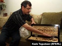 Евгений Жовтис показывает инкрустированные нарды ручной работы, которые ему подарили заключенные. Алматы, 11 апреля 2012 года.
