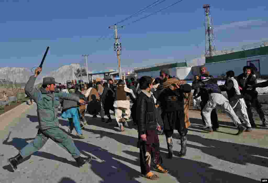 An Afghan policeman uses his baton to disperse demonstrators during a Kabul protest on February 24.