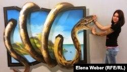 3D суреттер көрмесінің үйлестірушісі Екатерина Литвинова үш өлшемді форматтағы салынған суреттің жанында тұр. Қарағанды, 6 тамыз 2014 жыл.
