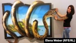 Координатор выставки 3D-картин Екатерина Литвинова демонстрирует посетителям, как выбрать правильный ракурс, чтобы на фотографии был отчетливо виден эффект трехмерного изображения. Караганда, 6 августа 2014 года.