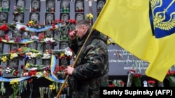 "UKRAINE -- An activist of Maidan holding a flag, makes the sign of the cross as he pays a tribute at the Maidan activists memorial also called the ""Heroes of the Heavenly Hundred"", referring to the people killed during the anti-government demonstration of"