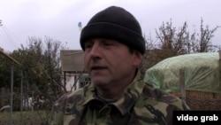 Володимир Балух на подвір'ї свого будинку з українським прапором, архівний відеокадр