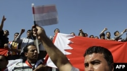 Demonstrators hold a Bahraini flag to denounce a crackdown on Shi'ite-led demonstrators in Bahrain in Baghdad on March 18.