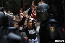Демонстранты и полиция на улицах Барселоны в день признанного незаконным референдума о независимости Каталонии 1 октября