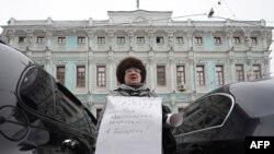 Русија, жена протетсира пред белоруската амбасада во Москва во знак на поддршка на притворените во Белорусија