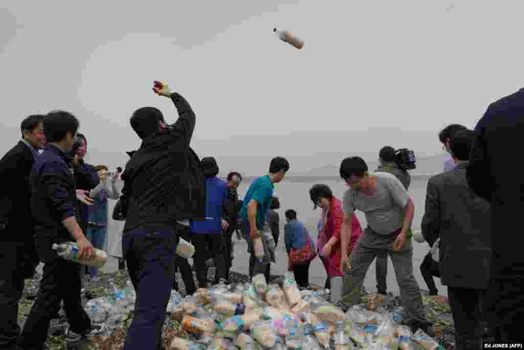 Bottles containing rice, money, and USB sticks are thrown into the sea by North Korean defector activists on Ganghwa island, west of Seoul, on May 1. The defectors have been throwing hundreds of bottles filled with food, cash, medicine, and memory sticks into the sea twice a month for more than two years. South Korean coast guards have told them the bottles are often retrieved by North Korean fishing boats. (AFP/Ed Jones)