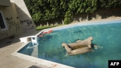 An armchair and furniture float in the swimming pool of the U.S. consulate in Benghazi following an attack on the building late on September 11, 2011, which resulted in the deaths of the U.S. ambassador to Libya, Chris Stevens, and three other US nationals.
