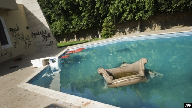 An armchair and furniture float in the swimming pool of the U.S. consulate in Benghazi following an attack on the building in September 11 in which the US ambassador to Libya and three other US nationals were killed.