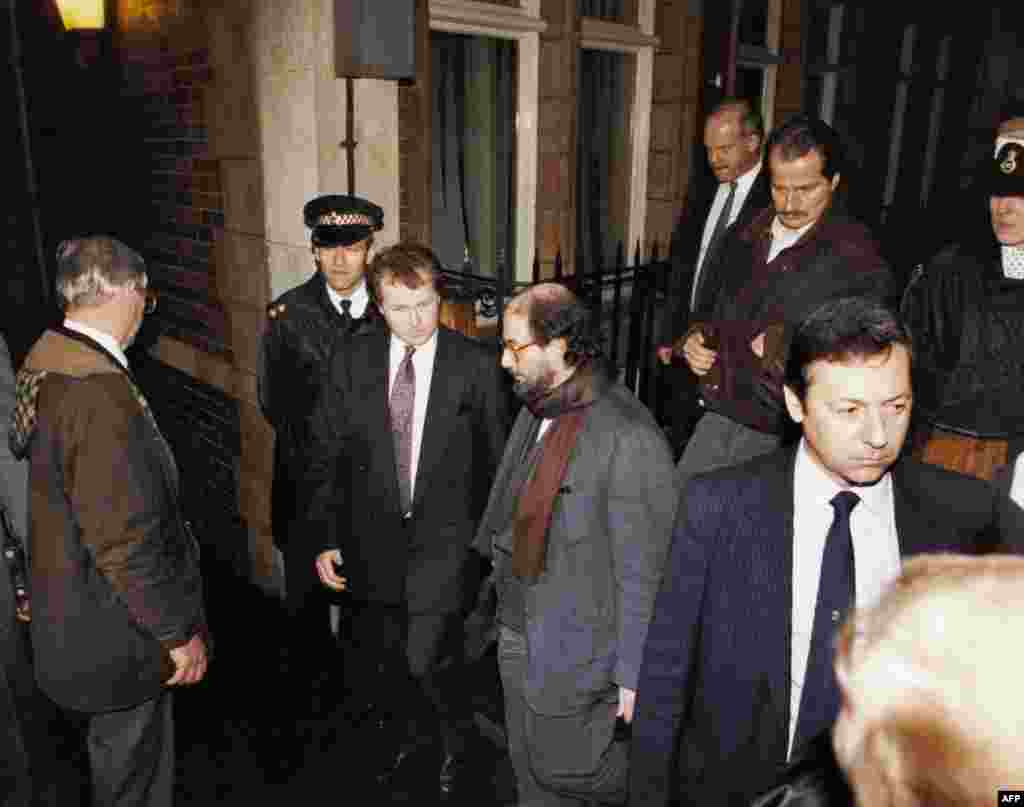 Rushdie is surrounded by police and bodyguards as he leaves Stationers Hall in London by a rear exit in 1992, three years after the fatwa was issued.