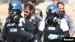 UN chemical weapons experts wearing gas masks carry samples from one of the sites of an alleged chemical weapons attack in the Ain Tarma neighbourhood of Damascus in August.