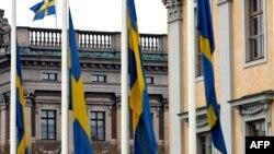 Շվեդիայի դրոշները երկրի արտգործնախարարության շենքի դիմաց և խորհրդարանի՝ Ռիկսդագի շենքի վրա, Ստոկհոլմ, արխիվ