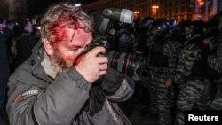 Украина милициясының операциясы кезінде басынан жараланған Reuters фототілшісі Глеб Гаранич Тәуелсіздік алаңындағы оқиғаны суретке түсіріп тұр. Киев, 30 қараша 2013 жыл.