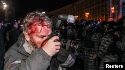 Ukraine -- Wounded Reuters photographer Gleb Garanich, who was injured by riot police, takes pictures as riot police block protesters during a demonstration in support of EU integration on Independence Square in Kyiv, November 30, 2013