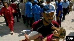 یک عراقی در حال بردن دختر مجروح خود به بیمارستانی در کرکوک در روز شنبه