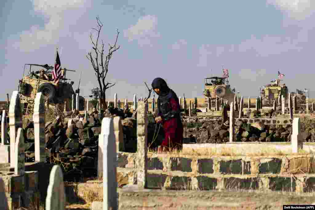 A Syrian woman visits a cemetery as U.S. armored vehicles patrol the northeastern town of Qahtaniyah near the border with Turkey. (AFP/Delil Souleiman)