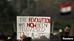 Egyptian protesters hold up a sign outside the Egyptian television center in Cairo in February during antigovernment protests. Al-Jazeera in many ways led the coverage of the protests.
