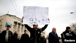 "An anti-government protester holds a placard reading, ""Europe, you owe us, do you remember 1992-1995?"" during a protest in Sarajevo."