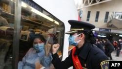 Проводник поезда общается жестами с медицинским работником, отправляющейся в Ухань