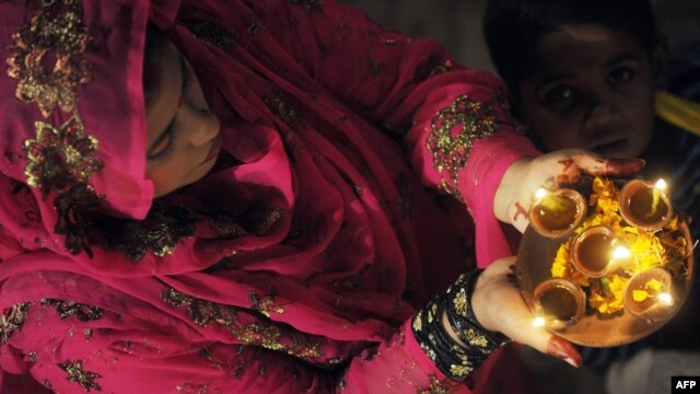 A Pakistani Hindu carries oil lamps on the occasion of Diwali. Sindh Province is home to most of Pakistan's small Hindu community.