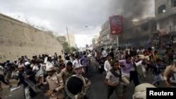 متظاهرون يهربون من رصاص الشرطة التابعة للحوثيين في مدينة تعز، 23 آذار 2015