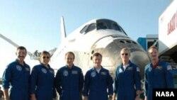 После благополучного возращения на Землю экипаж Atlantis позирует перед шаттлом.