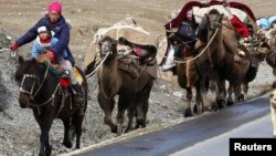 Казахи Синьцзян-Уйгурского автономного района Китая во время кочевки на летние пастбища. 23 сентября 2010 года. Иллюстрационное фото.