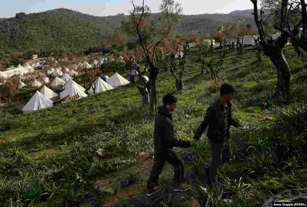 Мужчины из Афганистана идут через оливковую рощу рядом с импровизированным лагерем для беженцев.