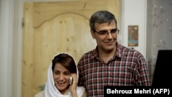 IRAN -- Lawyer Nasrin Sotoudeh (L) speaks on the phone next to her husband Reza Khandan as they pose for a photo at their house in Tehran, September 18, 2013