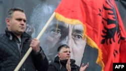 A man waves an Albanian flag next to a banner of former Kosovar Prime Minister Ramush Haradinaj during a protest staged by Kosovo war veterans' associations in support of the ex-guerrilla commander who is currently being detained in France.