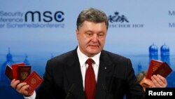 Ukraine's President Petro Poroshenko holds up Russian passports to prove the presence of Russian troops in Ukraine as he addresses the Munich Security Conference on February 7.