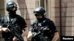 Armed police officers stand outside a residential property near to where a man was arrested in the Chorlton area of Manchester, Britain