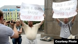 Journalist Sergei Duvanov and rights activist Andrei Sviridov hold signs on Almaty's main square