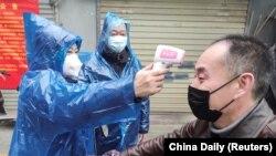 امدادگران در حال اندازهگیری دمای بدن یک شهروند چینی در ووهان، مرکز استان هوبی