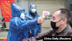 A worker takes body temperature measurement of a man at the entrance to a residential compound following an outbreak of the new coronavirus in Wuhan, Hubei province, February 1, 2020
