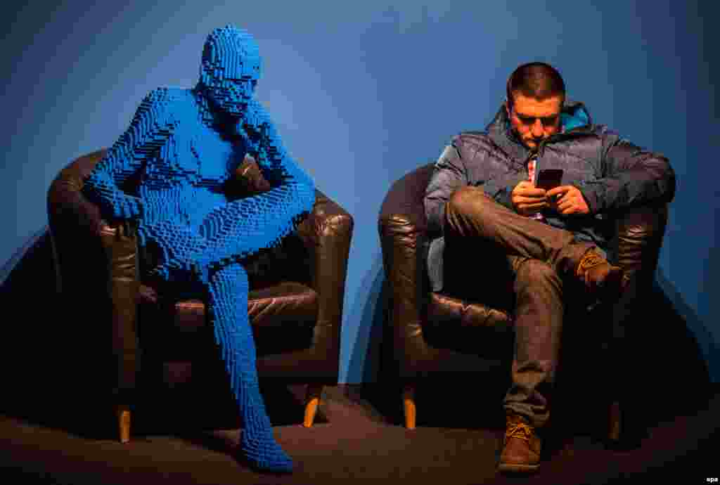 A visitor sits next to an artwork titled Blu Guy Sitting, made from 21,682 Lego bricks by U.S. artist Nathan Sawaya in Moscow. (epa/Sergei Ilnitsky)