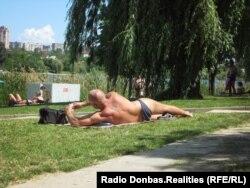 Донецк. Пляж у реки Кальмиус, мужчина загорает