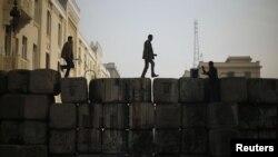 مصريون يسيرون فوق حاجز كونكريتي أمام وزارة الداخلية بالقاهرة
